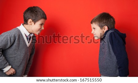 Young brothers arguing against red background.