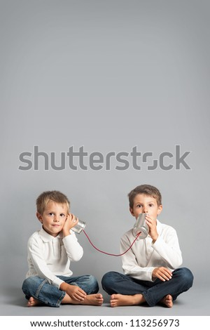 Young brothers talking with tin can telephone.