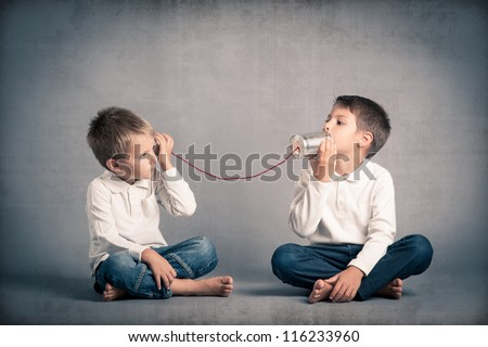 Young brothers talking with tin can telephone on grunge background. - stock photo