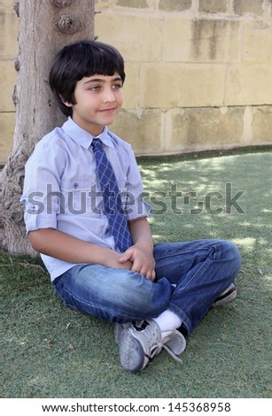 young brown haired boy sitting cross-legged by a tree - stock photo