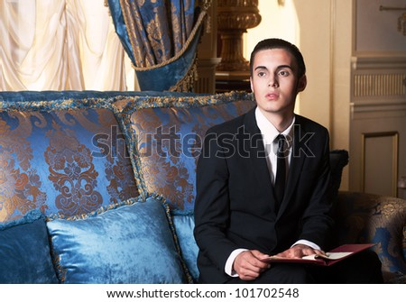 Young brunet man in blue royal interior, sitting on the sofa. - stock photo
