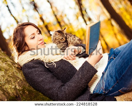 young brunet with cats reading book at fall forest tree - stock photo