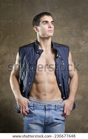 Young brunete sexy man posing shirtless with jacket showing abdominal and pectoral muscle. - stock photo