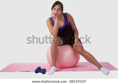 Young brunette aboriginal teen girl wearing workout attire sitting on big pink ball looking bored - stock photo
