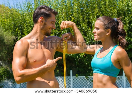 Young brunette athlete in sportswear, measures the biceps of muscular shirtless man at the park. Healthy lifestyle and fitness concept. - stock photo