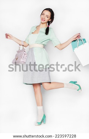 Young brunette beautiful woman dancing in pink dress isolated over white background - stock photo