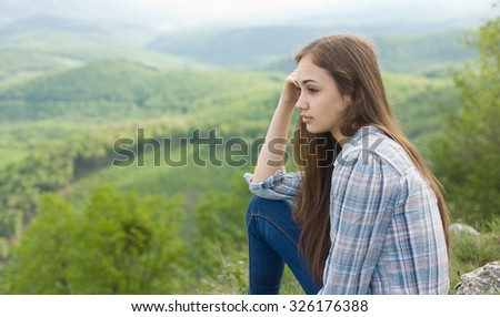 Young brunette beauty looking over the view with thoughtful expression. - stock photo