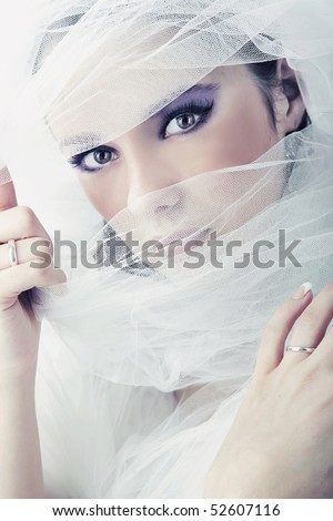 Young brunette beauty or bride, behind a white veil - stock photo