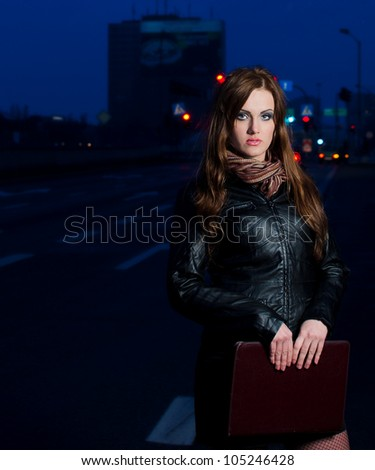 Young brunette business woman holding briefcase in the cite centre at night