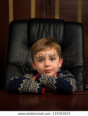Young brunette caucasian boy with bangs sitting in black leather chair at wooden desk - stock photo