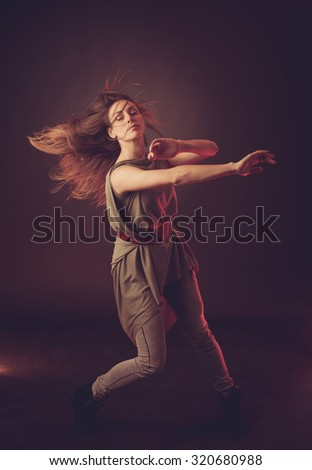 Young brunette caucasian woman dancing and her hair flowing through the air - stock photo
