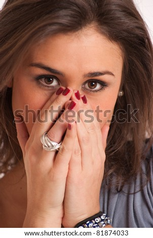 Young brunette covering her face with her hands - stock photo