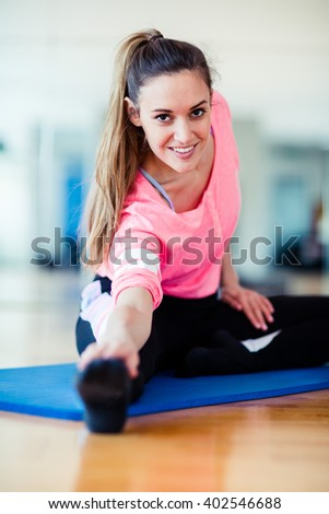 Young brunette european white caucasian girl exercising alone in gym with wooden floor doing yoga, pilates and fitness exercises