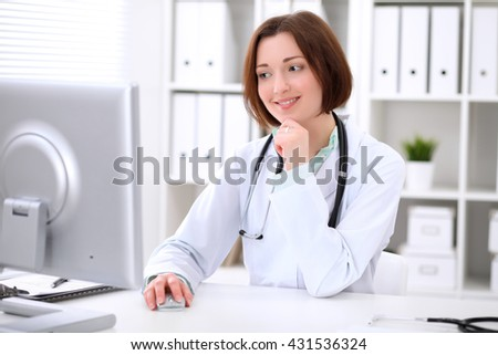 Young brunette female doctor sitting at a desk and working on the computer at the hospital office.  Health care, insurance and help concept. Physician ready to examine patient - stock photo