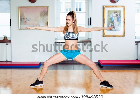 Young brunette female student in her 20s exercising at studio / gym with blue pants and black and white dotted sports top - stock photo