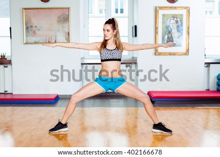 Young brunette female student in her 20s exercising at studio / gym with blue pants and black and white dotted sports top