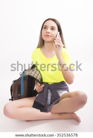 Young brunette female student sitting and calls the smartphone. Beautiful young backpacker - stock photo