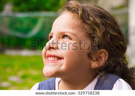 Young brunette girl closeup looking upwards and smiling cleverly. - stock photo
