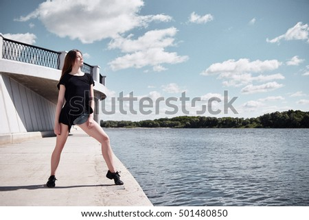 Young brunette girl dancing outdoors on grunge background