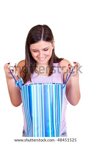 young brunette girl holding bag with stripes and looking surprised