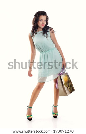 Young brunette girl in blue dress with shopping bag on a white background