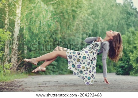 stock photo young brunette girl in colorful dress levitating in the park green trees lit with bright summer 204292468 woman levitating stock images, royalty free images & vectors  at bayanpartner.co