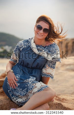 young brunette girl in short grey frock with lace and sunglasses sits on rock and shows legs against resort city