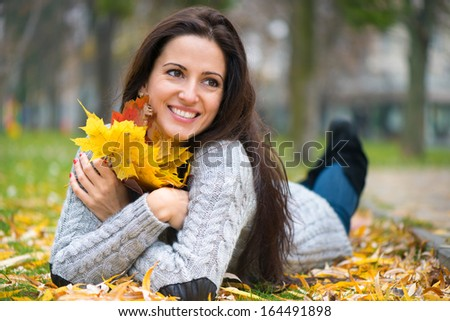 Young brunette girl lying at autumn park - stock photo