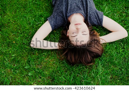 young brunette girl lying on the grass with his eyes closed