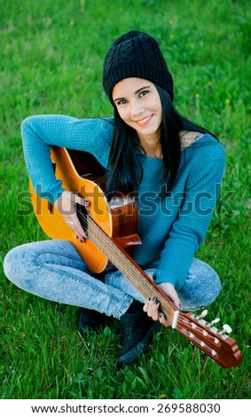 Young brunette girl playing guitar sitting on the grass - stock photo