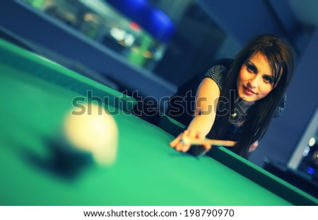 Young brunette girl playing snooker - stock photo