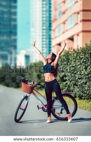 Young brunette girl posing in summer on a retro pink bike posing outdoors on a Sunny day