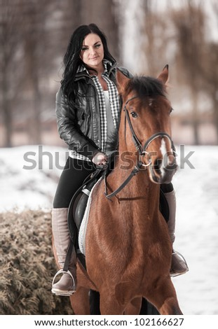 Young brunette girl riding horse