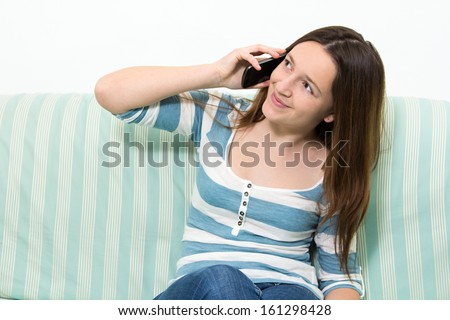 Young brunette girl with a blue and white striped top talking on the phone - stock photo