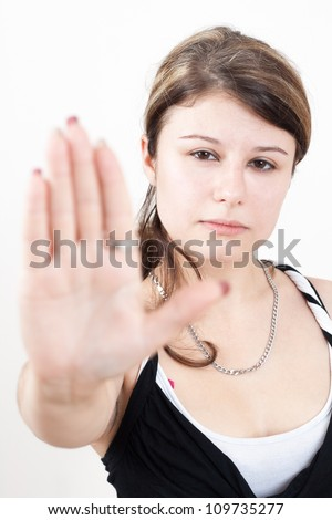 young brunette girl with brown eyes is showing the stop gesture on white background