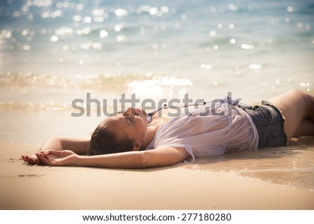 young brunette girl with naked bust in wet white blouse lies on her back near water edge against gleam of water