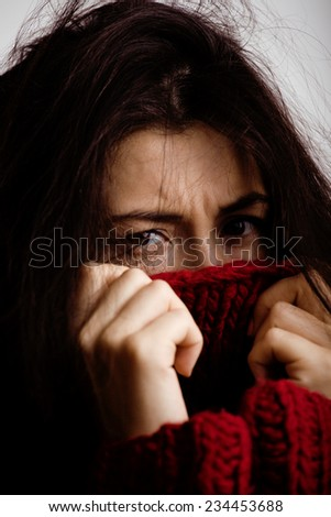 young brunette gloomy woman in sweater all over her face, messed hair close up - stock photo