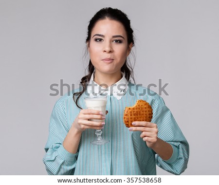 Young brunette in a blue shirt chewing cookie , keeping a glass of milk in the hand