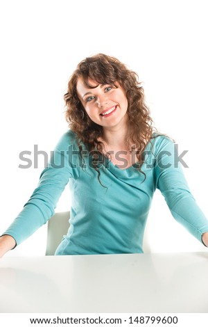 Young brunette in a turquoise dress posing in the studio - stock photo