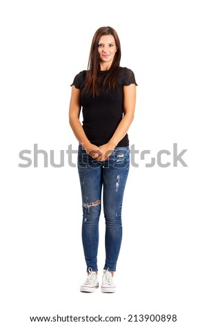 Young brunette in modern casual clothes holding her hands. Full body length isolated over white. - stock photo