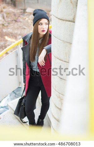 Young brunette in stylish winter coat and winter cap with serious look on her face. Standing on spiral staircase and leaning on her arm.