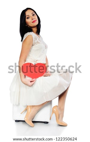 Young brunette in white dress with red Valentine heart isolated on white background - stock photo