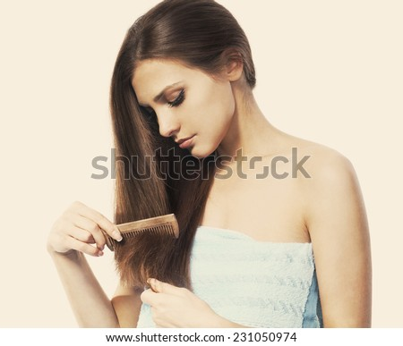 Young brunette lady combing her beautiful long hair - stock photo