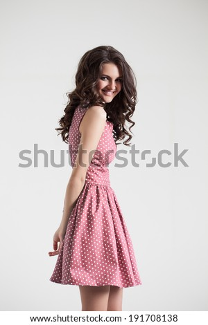 Young brunette lady in color dress. Fashion portrait in studio. Sexy beautyful dress - stock photo