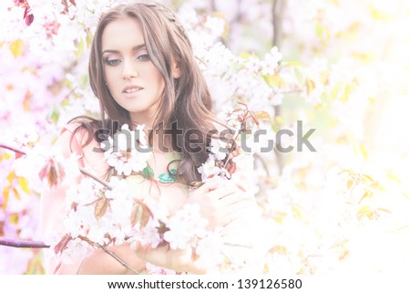 Young brunette lady in flowers of sakura - stock photo