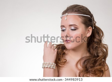 Young brunette lady with beautiful hair and ornaments on a gray background