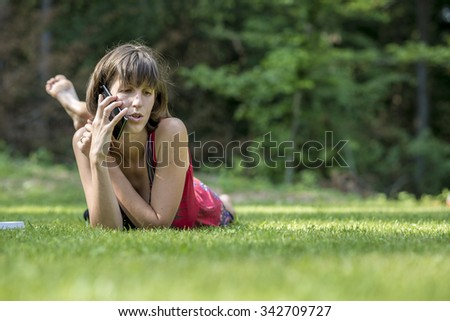 Young brunette lying in green grass leaning on her arms as she talks on mobile phone.