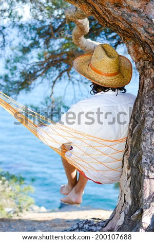 young brunette man in a hat white shirt having fun relaxing relaxing sitting in a hammock on the beach under a tree dreaming & looking into the distance on blue sea copy space background image - stock photo