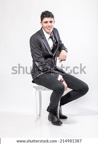 Young brunette man in suit sitting on chair and smiling