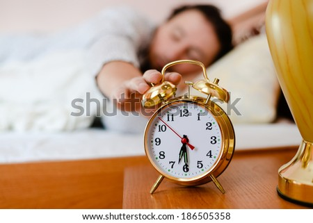 young brunette man pulling his hand off the bed to the alarm clock on the foreground - stock photo